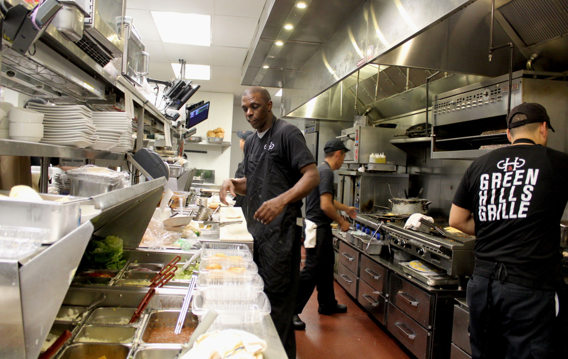 <p>Line cooks prepare meals for the dinner crowd at Green Hills Grille. Photo by Rover/Dylan Skye Aycock</p>