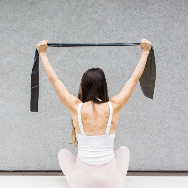 a woman does Pilates with an exercise band