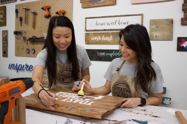 From left: Gina Nguyen and Lisa Tan offer craft workshops where participants can create wood signs, paint doormats and more. (Taylor Jackson Buchanan/Community Impact Newspaper)