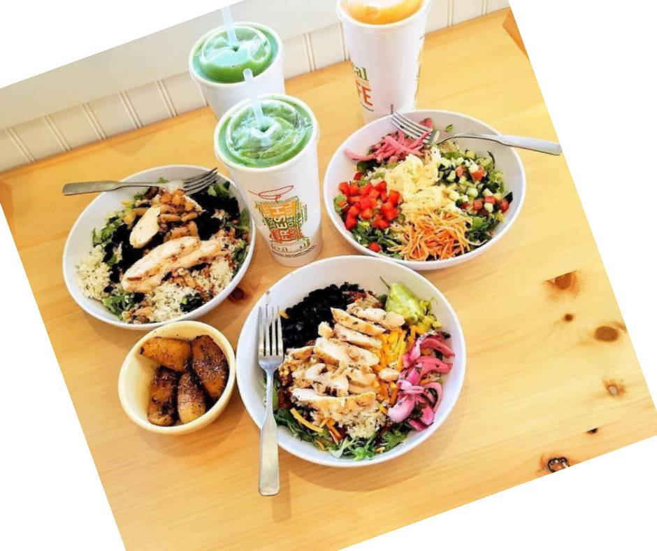 three salads in white bowls on a food plank with three smoothies
