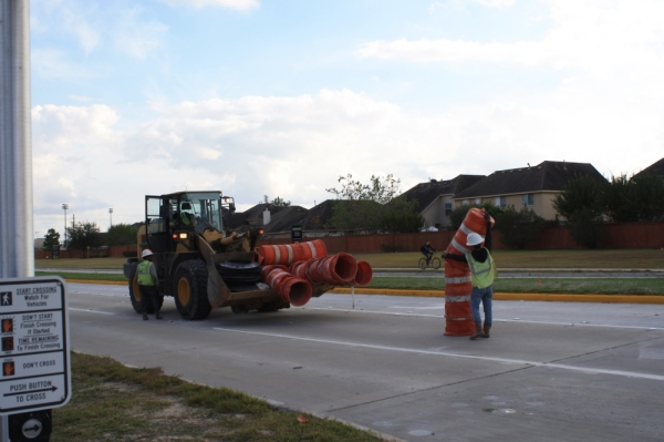 Construction crews move traffic cones on Gaston Road, which is expected to be completed before Thanksgiving. (Jen Para/Community Impact Newspaper)