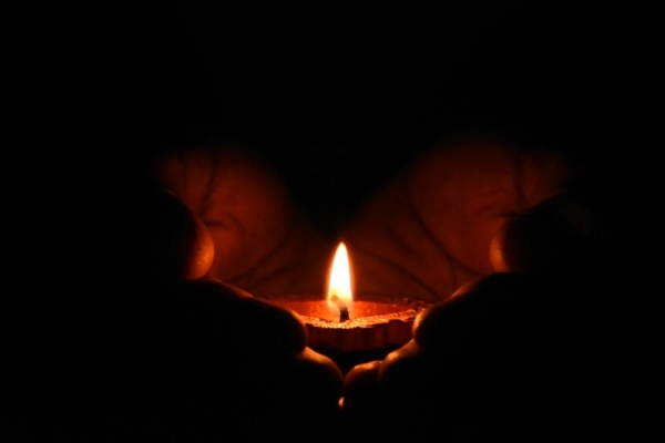 two hands holding a lit candle in the dark