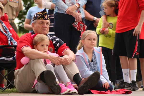 A veteran and children watch a Veterans Day ceremony in 2016. (Lindsey Juarez Monsivais/Community Impact Newspaper)