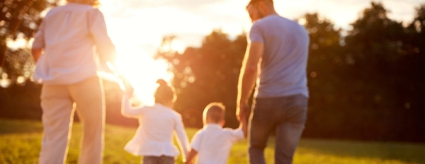 family walking in the park at sunset