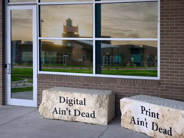 """Community Impact Newspaper already has a large stone outside of its printing facility that reads, """"Print Ain't Dead."""" This photo illustration shows that mantra extends to the online product. (Photo illustration by Derek Sullivan)"""