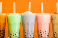 a bunch of boba tea drinks on an orange background