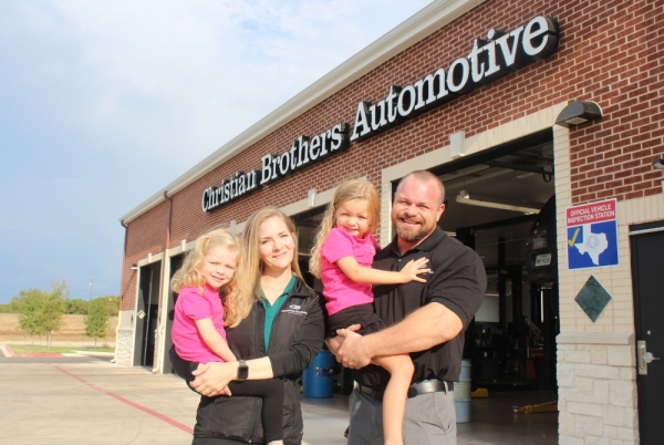Crystal and Brad Escue hold their two daughters, Madeline (left) and Hannah, at their business, Christian Brothers Automotive in Leander, which recently celebrated its one-year anniversary. BRIAN PERDUE/COMMUNITY IMPACT NEWSPAPER