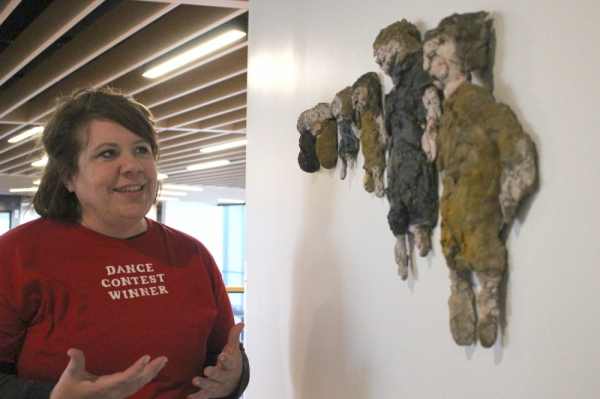 "Artist Julia Jalowiec talks about her sculpture ""Evolution of Sisters,"" which depicts the growth of her and her own sister. (Renee Yan/Community Impact Newspaper)"