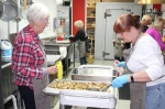 Volunteers help prepare lunch for those in need. (Photo by Anna Herod/Community Impact Newspaper)
