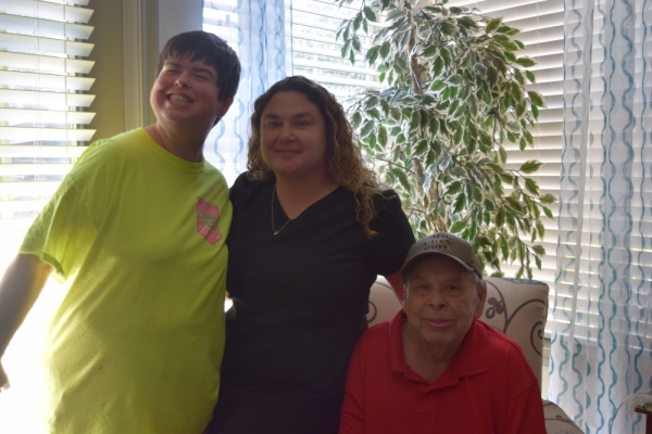 Caregiver Carroll Toombs (center) provides care to Eleah (left), James (right) and Betty Anderson. (Emily Davis/Community Impact Newspaper)