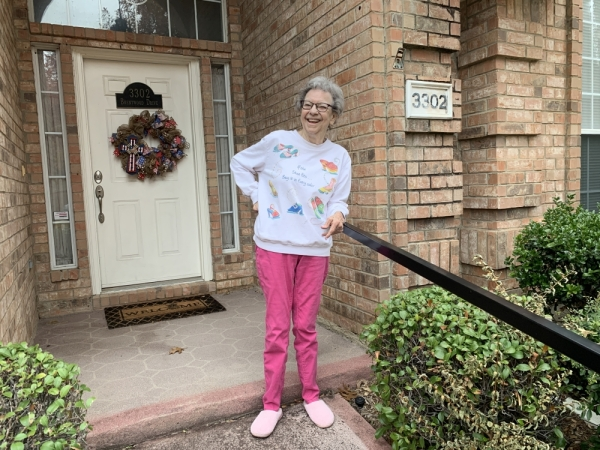 Homeowner and widow Marilyn Walker is thankful for the work of Seniors Helping Seniors. She shows off the handrail recently installed on her front sidewalk. (Jean Ann Collins/Community Impact Newspaper)