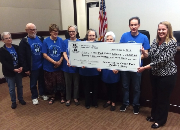 Friends of the Cedar Park Library presented a ceremonial check for $20,000 to the library at the City Council meeting Dec. 5: (from left) Friends members Shira Ledman, Bob Ledman, Vera Vasudevan, Margi Leake, Treasurer Pat Watson, Susie Andrews and President Mike Kredt. Library Director Julia Mitschke is seen at right. (Brian Perdue/Community Impact Newspaper)