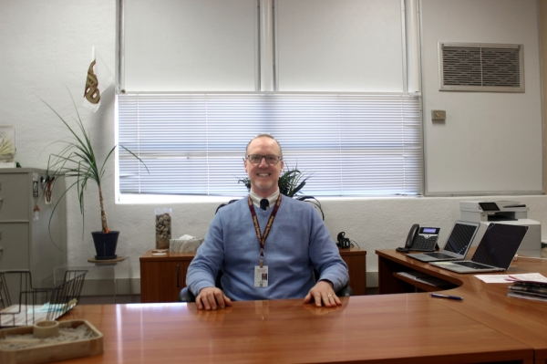 A photo of Todd Washburn sitting behind a desk.