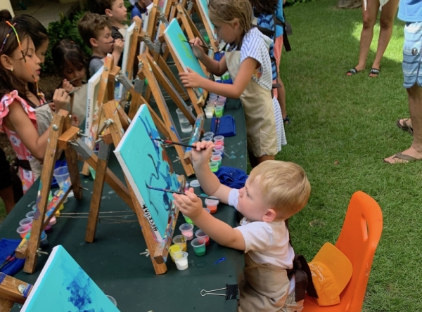 kids painting on easels in the grass