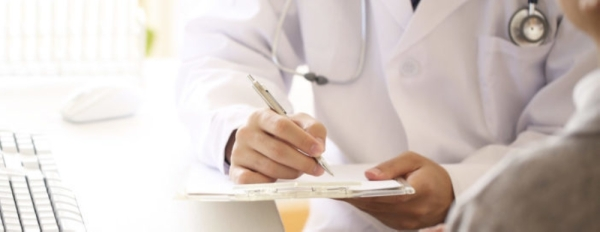 doctor in white coat writing on notepad