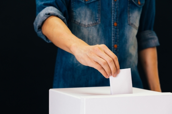 person in denim shirt with rolled sleeves puts ballot in ballot box
