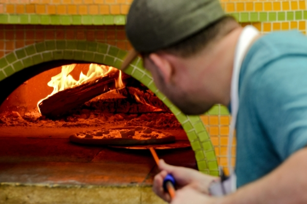 A photo of a man placing a pizza inside of a wood-fired oven.