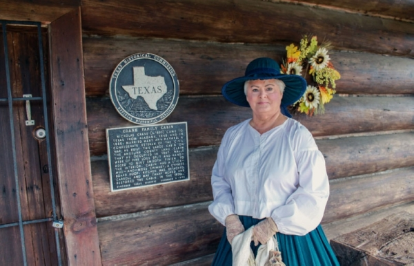 Docent Eva Rains stands by the cabin of her ancestors, Crane Cabin. (Andy Li/Community Impact Newspaper)