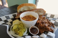 JL's Lone Star BBQ meal with meat and white bread and pickles and sauce on black and white checkered tablecloth