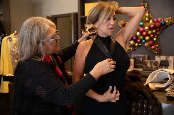 Judi Gugel adds a statement necklace to a black dress during a styling session with VIP Labels consigner Rose Wise.