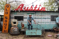 "Todd Sanders stands in front of his former home, a trailer in the courtyard of his South Austin studio and art gallery. He collects old signs, and the ""Austin"" one above the trailer is his favorite. Emma Freer/Community Impact Newspaper"