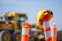orange traffic poles, one with a yellow hardhat on top