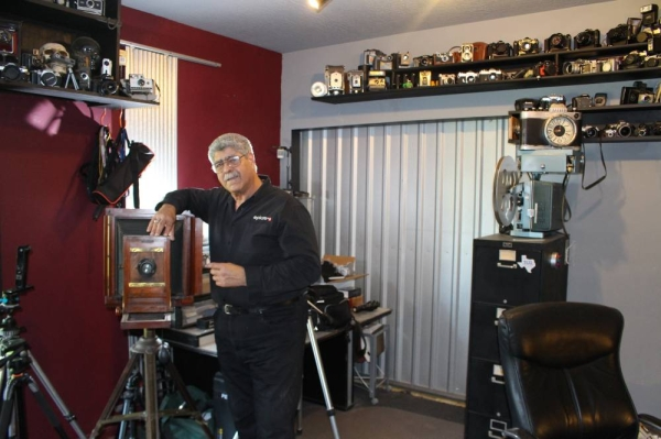 Vic Cherubini, president and founder of Epic Software Group and the Epic Creative Co-op, stands alongside a portion of his camera collection. Ben Thompson/Community Impact Newspaper