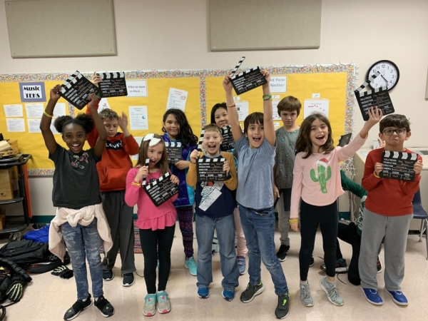 A photo of kids smiling and holding director's cut props.