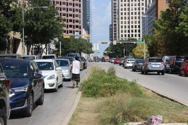 A man panhandles between lanes of traffic in downtown Austin during the summer of 2019. Christopher Neely/Community Impact Newspaper