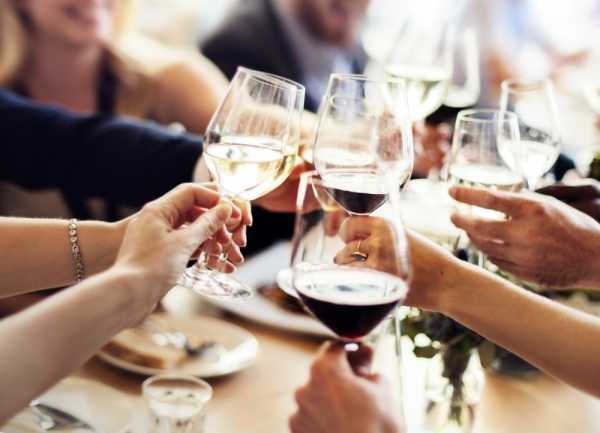 people cheers-ing with wine glasses at a table