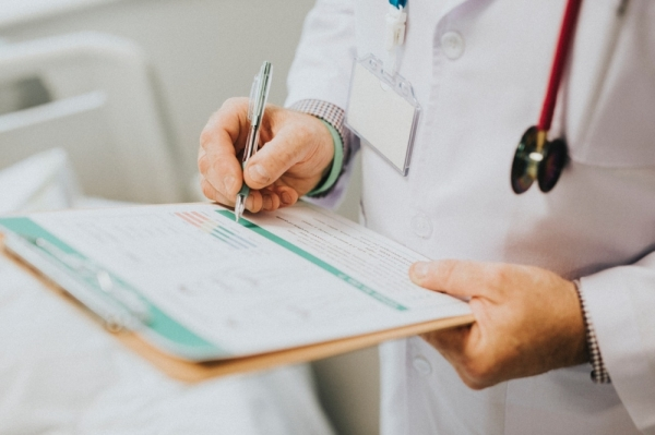 doctor writing on a clipboard adobe stock image
