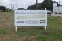 "A photo of a sign that reads ""Visit Historic Dripping Springs."""
