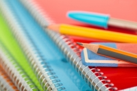 pencils and pens resting on a stack of spiral notebooks fotolia stock image