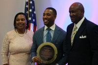 Chauncy Glover (center) accepts an award from Ann and T.J. Wilkerson. (Andy Li/Community Impact Newspaper)