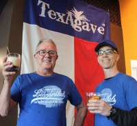 Leanderthal Distilling founder Scott Calame (right) raises a glass with bartender Jim Nunn. (Brian Perdue, Community Impact Newspaper)