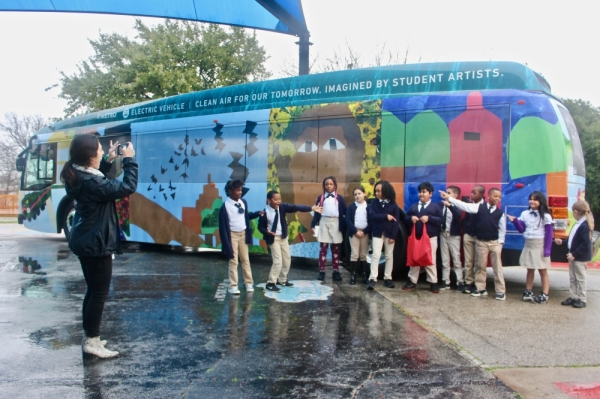 Students at Lee Lewis Campbell Elementary Media and Performing Arts Institute in East Austin point to their classmate holding the red bag, whose artwork is featured on the new electric bus. (Amy Denney/Community Impact Newspaper)