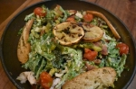 The Herban Caesar ($17) is a salad made with fresh greens, house-made Caesar dressing, bacon, grilled lemon, grilled scallions, roasted tomatoes, Brussels sprouts, toast points, Parmesan cheese and chicken. (Alex Hosey/Community Impact Newspaper)