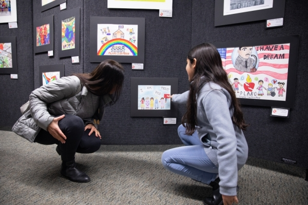 Nora Rotem, elementary school art finalist in the Martin Luther King Jr. diversity competition, shows her mother, Ori Rotem, her piece. Finalist and semifinalist art pieces filled the common area of Williams High School. (Liesbeth Powers/Community Impact Newspaper)
