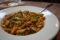 Reyes chipotle pasta is made with penne pasta, served with asparagus, red bell peppers, mushrooms, peas, cilantro and chicken in a spicy chipotle cream sauce. (Shawn Arrajj/Community Impact Newspaper)