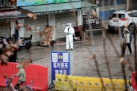 A worker in a protective suit stands near the closed seafood market in Wuhan, China. (Reuters/Darley Shen)