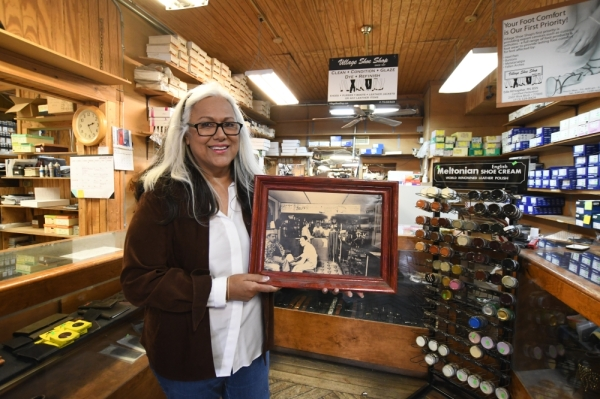 Owner Edie Almogabar poses with a photo of Village Shoe Shop from its first year of operation in 1947. (Photos by Hunter Marrow/Community Impact Newspaper)