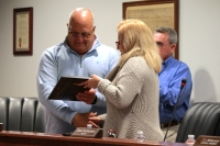 Former Council Member John Bickford receives a plaque from Mayor Sara Countryman in recognition of his service to the city. (Andy Li/Community Impact Newspaper)