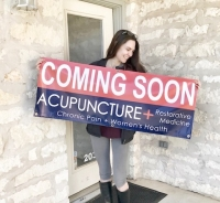 "A photo of a woman holding a ""coming soon"" sign for Acupuncture   Restorative Medicine"