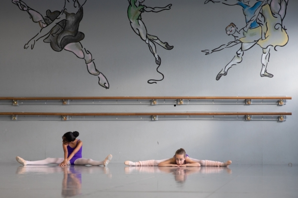 Level III ballet students take part in stretches during class. Before reaching Level IV, students must master technical skills and prove their physical and mental focus, according to the academy's syllabus. (Liesbeth Powers/Community Impact Newspaper)