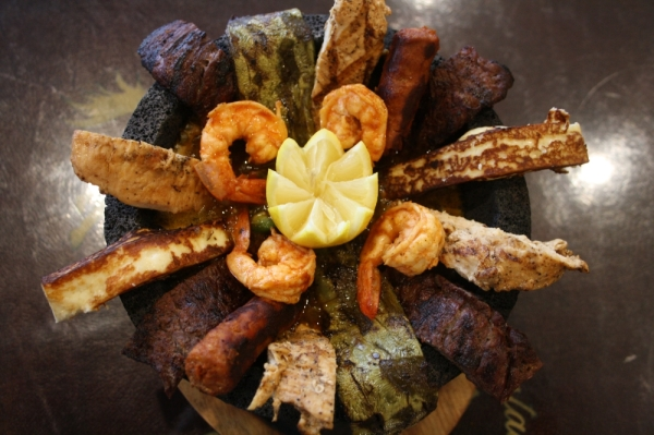 Lalo's Molcajete includes beef, chicken, shrimp, Mexican sausage, Mexican cactus and cheese served in a molcajete with hot sauce and the diner's choice of rice and beans. (Shawn Arrajj/Community Impact Newspaper)