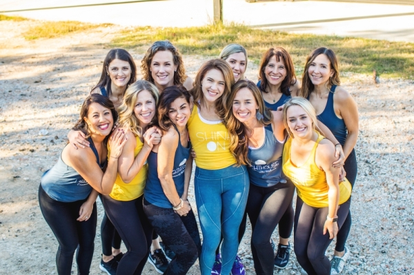A photo of a group of women huddled together in yellow and blue fitness gear.