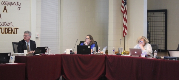 A photo of Ron Jones, Joanna Day, and Barbara Stroud at a board of trustees meeting.