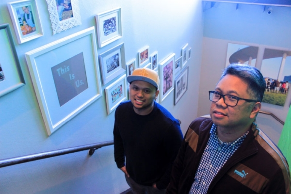 As diners come up the stairs to Be More Pacific, they pass the family photos of owners Giovan Cuchapin (left) and Mark Pascual. (Jack Flagler/Community Impact Newspaper)