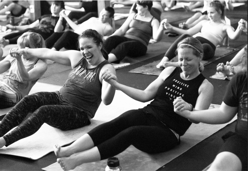 A photo of several women holding hands and doing yoga together.