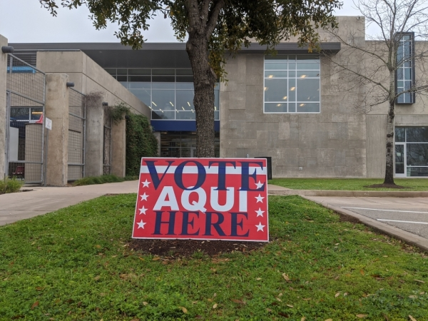 "A photo of a sign that reads ""Vote Here"" and ""Vote Aqui"""